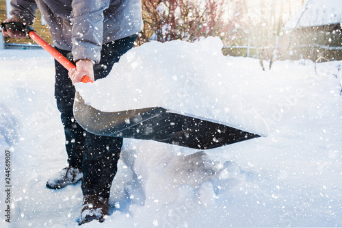 Fotografie, Obraz Man clearing snow by shovel after snowfall. Outdoors.