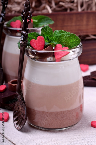 Fotografía  Three chocolate mousse dessert in a glass jar garnished with sugar hearts and mi