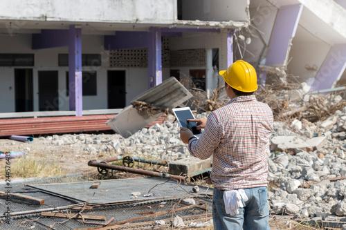 Fotomural Engineer holding tablet is checking for destruction, demolishing building