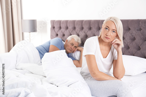 Fotografía  Mature couple with relationship problems ignoring each other in bedroom