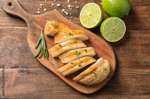Board with fried chicken breast and limes on wooden background, top view