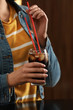 Woman holding glass of cola with ice against blurred background, closeup