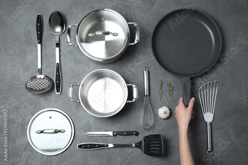 Fotomural  Woman holding frying pan over table with clean cookware, top view