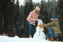 Couple Making Snowman Near Forest. Winter Vacation