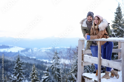 Couple spending winter vacation together in mountains. Space for text