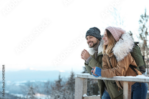 Couple with backpacks enjoying mountain view during winter vacation. Space for text