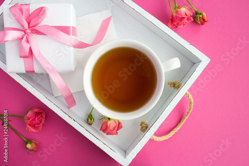 Tea in the cup and gift with pink bow on the white wooden tray on the dark pink  background.Top view.Closeup. - 244587014