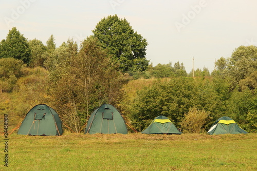 In line four green c& tents on the green grass on the forest background on summer & In line four green camp tents on the green grass on the forest ...