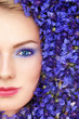 Close-up portrait of young beautiful blue-eyed woman with blue flowers around her face