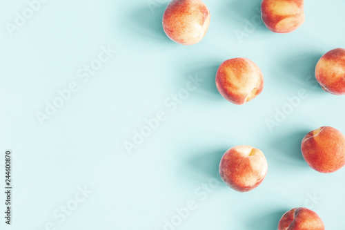 Peaches on pastel blue background. Frame made of fresh peashes. Flat lay, top view, copy space