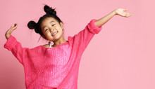 Asian Kid Girl In Pink Sweater, White Pants And Funny Buns Stands With Hands Up And Smiles. Close Up