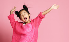 Asian Kid Girl In Pink Sweater, White Pants And Funny Buns Sings Singing Dancing On Pink