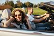 brunette riding cabriolet with boyfriend