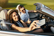 woman taking selfie with her boyfriend on smartphone in the cabriolet