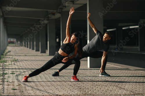 Fotografia  Young couple stretching legs in urban environment