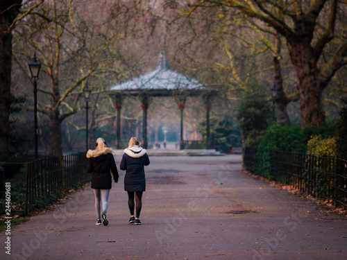 Photo Battersea Park's ornate Victorian bandstand in golden hour, with two women walki
