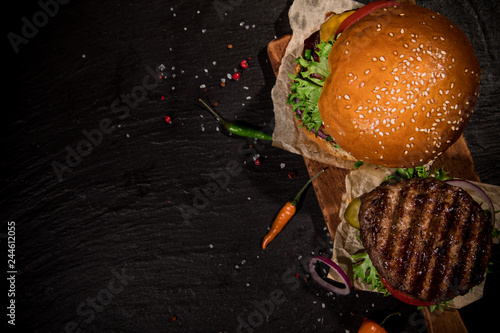 Top view of tasty burgers on wooden table.