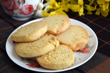 Delicious Homemade Cookies With Lemon Zest. Round Cookies Are Stacked On Top Of Each Other On A Plate. Close-up, Homemade Cakes In A White Plate On A Table With A Tablecloth