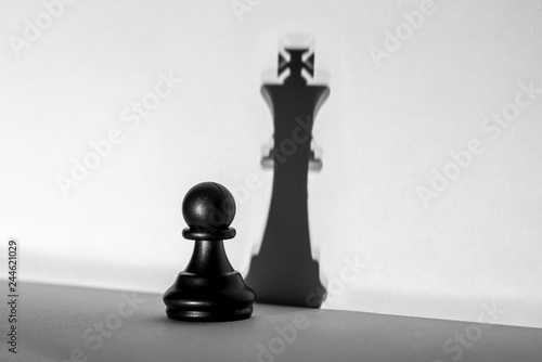 Fotografie, Obraz  Chess pawn standing in a spotlight that make a shadow of king with darkness arti