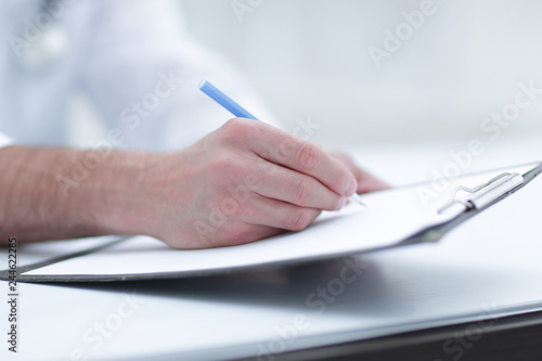 doctor writing out the prescription.close-up