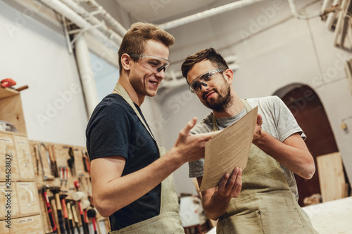 Two young men in aprons and goggles smiling and pointing at papers while working in modern joinery together