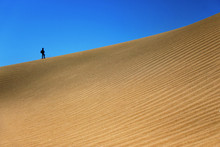 A Minimalism Of Maspalomas Sand Dunes In Gran Canaria. A Tiny Man In The Background Gives A Create Scale How Huge The Sand Dunes Are.