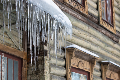 Foto  Ice stalactite hanging from the roof with wooden wall