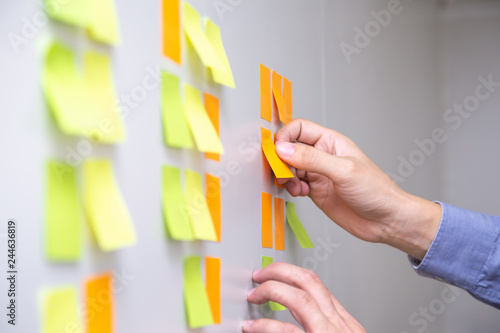 Photo IT worker tracking his tasks on kanban board
