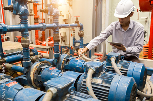 Fotomural  Asian engineer maintenance checking technical data of  system equipment Condenser Water pump and pressure gauge ,  water pump