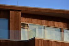 Facade With Windows And Veranda Of Modern Wooden House With Vertical Varnished Cladding And Glass Transparent Railing.