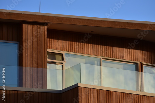 Fotografie, Obraz  Facade with windows and veranda of modern wooden house with vertical varnished cladding and glass transparent railing