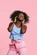 canvas print picture Portrait of a cool, happy young woman with blue curly hair, isolated on pink background
