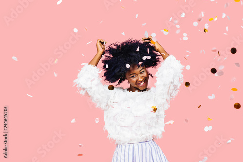 Fotografía  Portrait of a very happy young woman with black curly hair dancing amidst confet