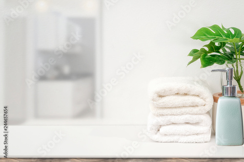 Fotografia  Mockup white towels and houseplant on white table with copy space for product display