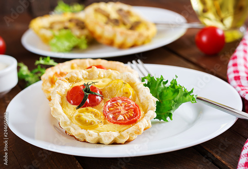Cheddar, tomatoes tartlets on wooden background. Mini pies. Delicious appetizer, tapas, snack.