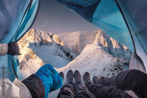 In de dag Kamperen Group of climber are inside a tent with open for view of blizzard on mountain