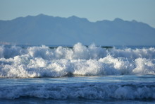 White Foam Of Oceanic Surf Rolling Towards Camera With Large Landmass In Distant Background.