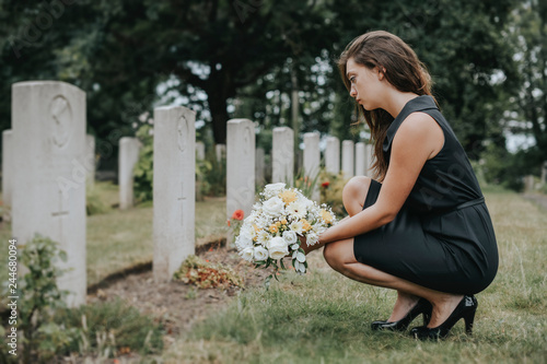 Photo Young widow laying flowers at the grave