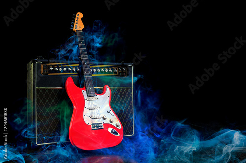 Foto Red electric guitar and amplifier surrounded by blue smoke on dark empty stage