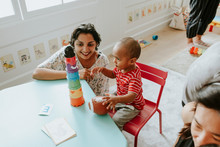 Child Playing With A Teacher In The Nursery