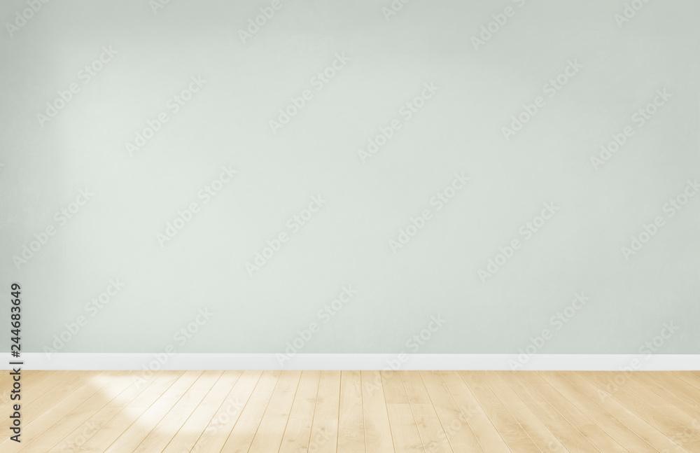 Fototapeta Light green wall in an empty room with a wooden floor
