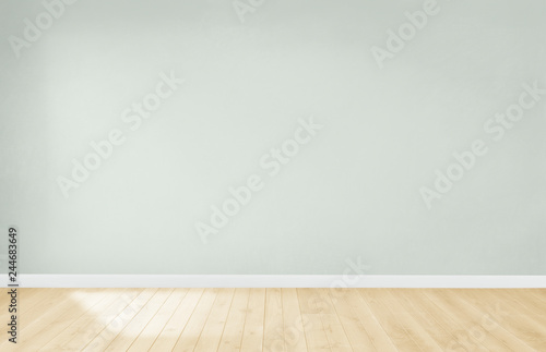 Door stickers Wall Light green wall in an empty room with a wooden floor