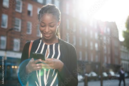 fototapeta na lodówkę Woman texting on her phone in the city
