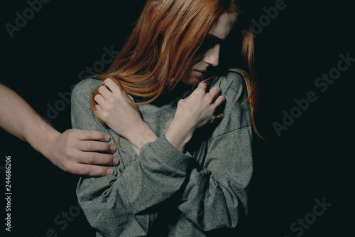 Stranger's hand put on scared young redhead woman's arm as a symbol of abuse Canvas Print