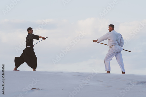Deurstickers Vechtsport Two men practicing Japanese martial arts in desert