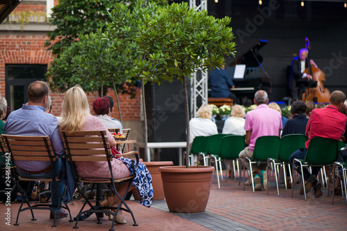 Платно Married couple is sitting in restaurant, drinking wine, eating fancy snacks and listening to jazz concert in concert venue in city square