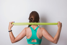 Woman Stretching Rubber Band Behind Her Back.
