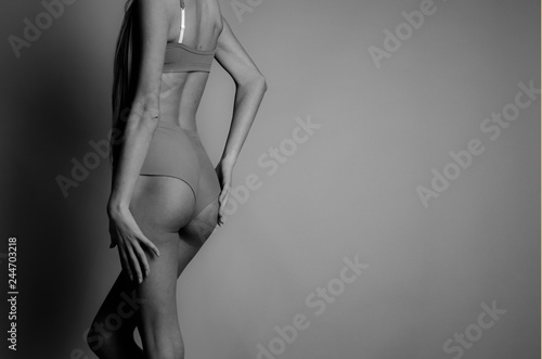 Fototapeta young, thin, sexy girl touches her body and lingerie during a photo shoot in a photo studio obraz na płótnie
