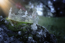 Mysterious And Magical Photo Of Silver King Crown Over The Stone Covered With Moss In The England Woods Or Field Landscape With Light Flare. Medieval Period Concept.
