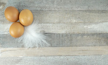 Brown Chicken Eggs With Feather At Wooden Background